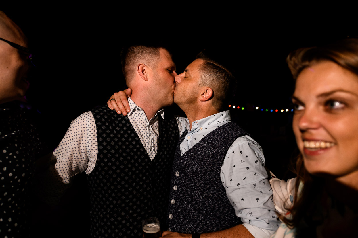 Kussend bruidspaar tijdens het feest
