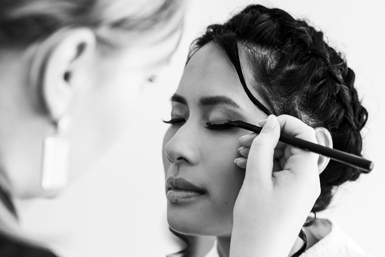 de make-up van de bruid wordt gedaan