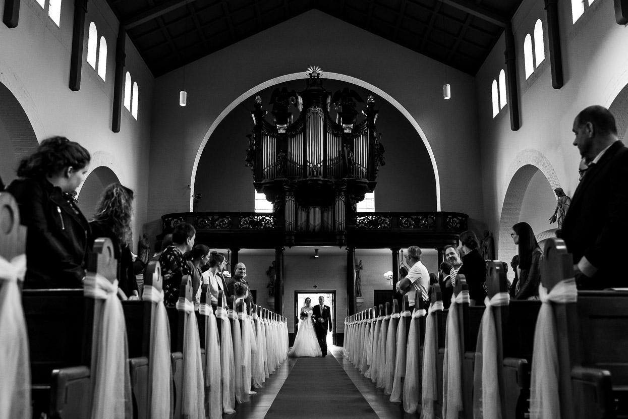 de bruid komt aan de arm van haar vader de kerk binnen