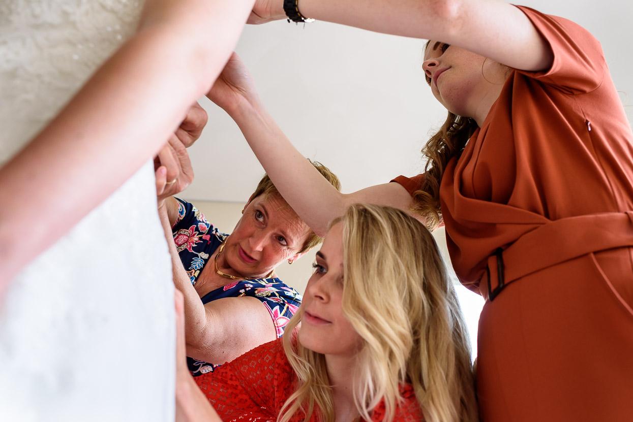 bruidsmeisjes helpen met aankleden