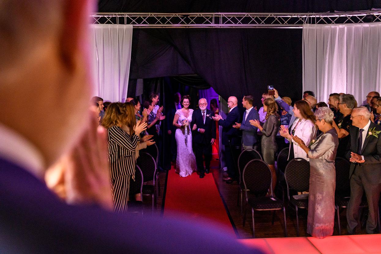 de bruid komt de ceremoniezaal binnen aan de arm van haar vader