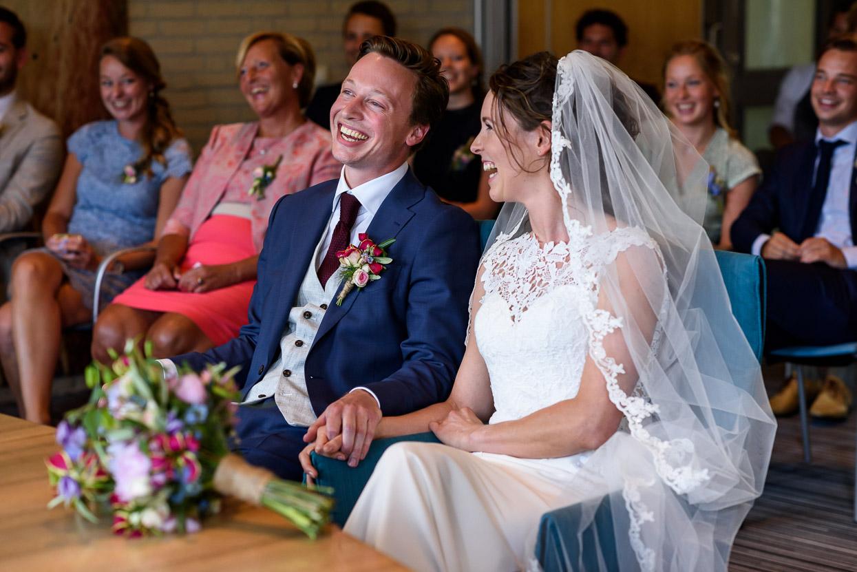 bruidegom en bruid tijdens ceremonie met bloemen